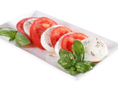 Plate of mozzarella cheese, tomatoes and basil